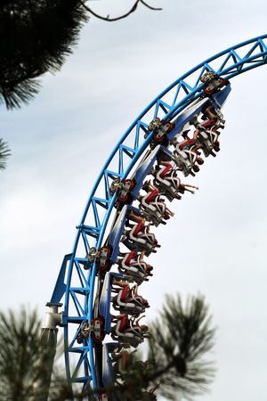 people in the looping of a fast roller coaster Stock Photo