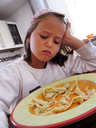 no gustar: ni�a no quiere comer sus fideos Foto de archivo