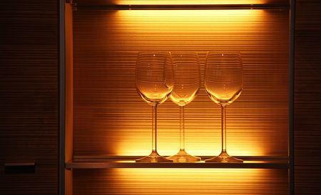 any glasses on a shelf of a pub with light photo