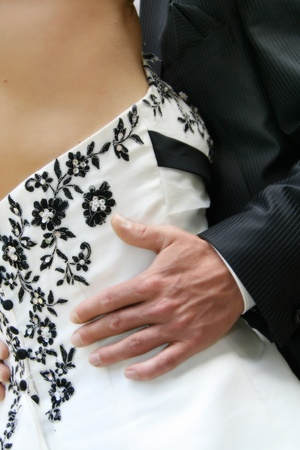 Bridgrooms hand on brides dress on the dance photo