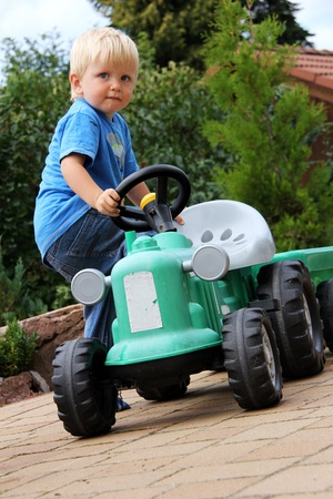 nice little blonde boy with green tractor toy photo