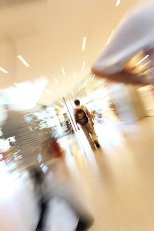 leaving: blurred unrecognizable people in motion in a shopping mall Stock Photo