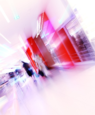 blurred unrecognizable people in motion in a shopping mall photo
