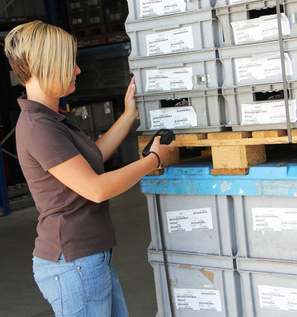 worker scans pallets and boxes in the warehouse photo