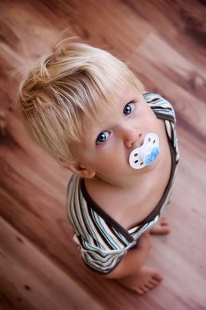 jeunes petit garçon est à la recherche sur le plancher de bois