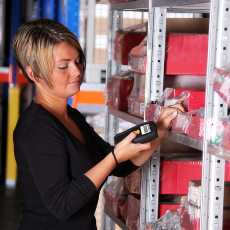 codigos de barra: trabajador escanea paletas y cajas en el almacén