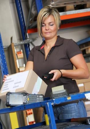 werknemer scant pallets en dozen in het magazijn Stockfoto