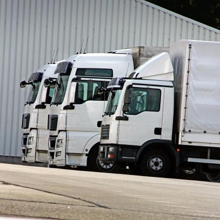 parked: drie witte vrachtauto's staan te wachten in een rij