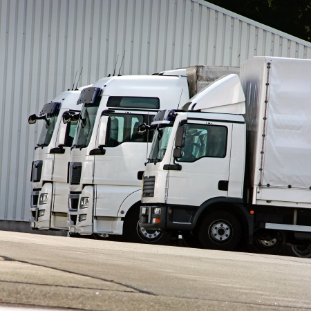 three white trucks are waiting in a row