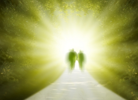 person walking: Two people are walking into the light of the paradise
