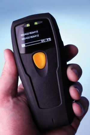 hand is holding a handheld barcode scanner photo
