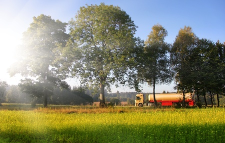 agrofuel  lorry is driving on the street in the near of a field of rape  photo