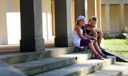 two childrens are sitting in front of an old pathway with pillars Stock Photo - 10822473