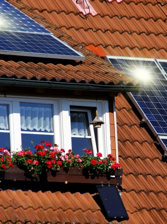 Housetop with solar an flowers on the window photo