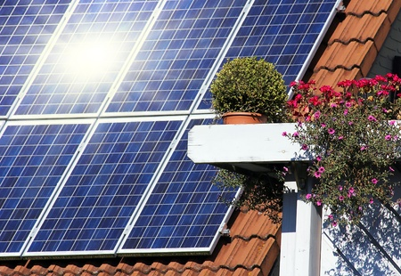 photovoltaic: Housetop with solar an flowers on the window
