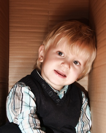 little boy is standing in the brown box alone Stock Photo - 11168244