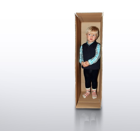 little boy is standing in the brown box alone photo
