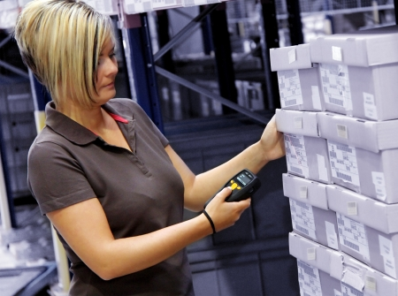 inventories: worker scans pallets and boxes in the warehouse Stock Photo