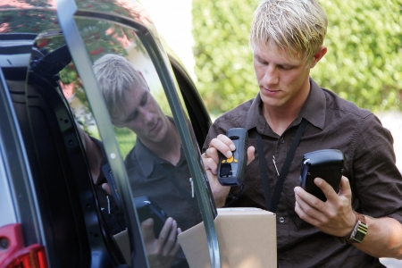 handheld device: Delivery service man is scanning barcode