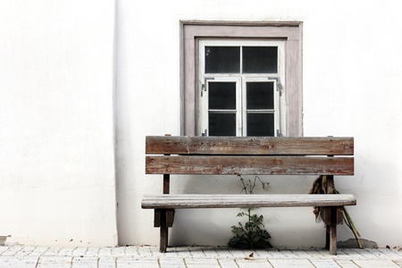 old bench in front of an weathered window with white wall Stock Photo - 12861925