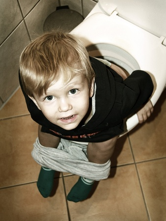 little boy is sitting on the toilet photo