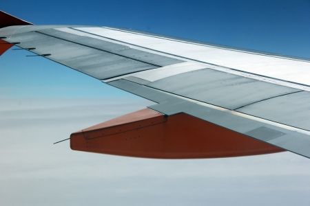 The wing of an aeroplane with orange parts in the sky Stock Photo - 15178487
