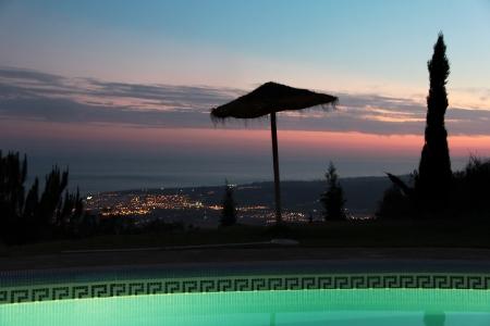 Scène tranquille avec parasol de paille et beau coucher de soleil Banque d'images - 15501395