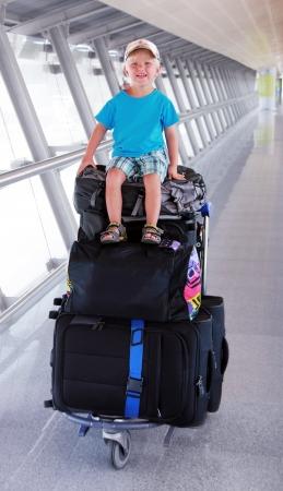 Jeune garçon est assis sur le fourgon à bagages Banque d'images - 15264766