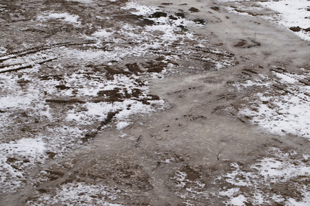 mud and snow: dirty frozen ground with snow background Stock Photo