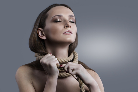 girl tied: Glamorous portrait of a girl tied to your problem, a big thick rope. Beautiful makeup interesting light.