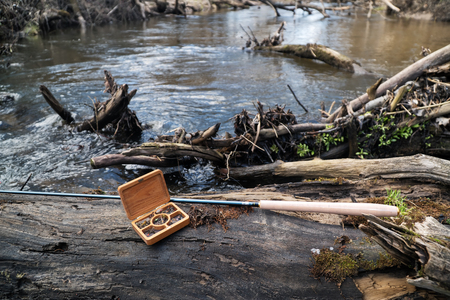 The fishing rod and the box with flies lie on a fallen tree with a view of the river. Street shooting early spring. Stock Photo