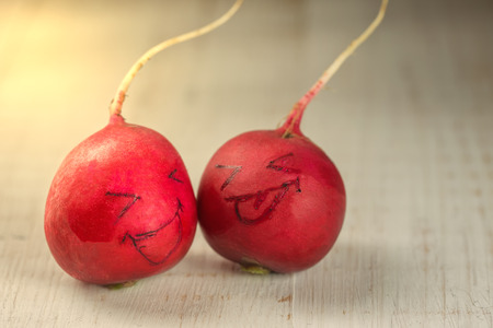 Two radish heads with painted smiles