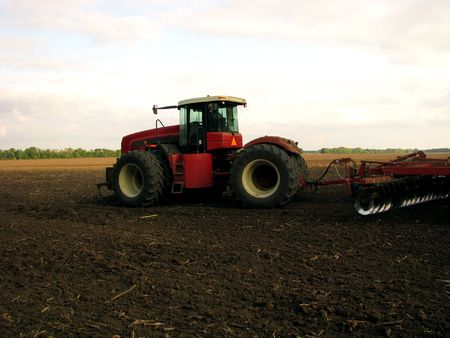 wheeled tractor: wheeled tractor harvesting field. nature background. rural background