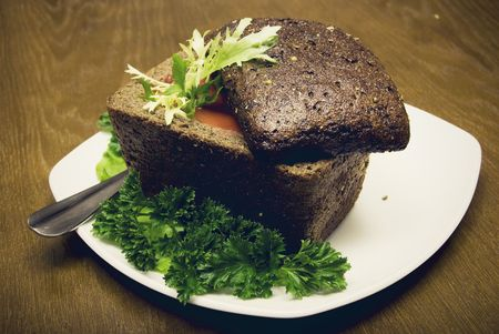 Red soup in a loaf of brown bread photo
