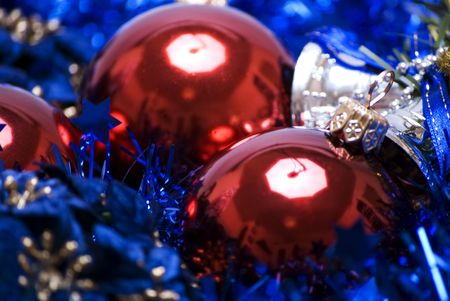 Red Christmas balls with blue tinsel and silver bell close-up photo