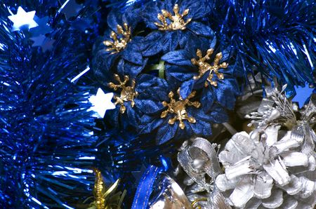 silver bells: Christmas blue tinsel, silver bells,decorative cone and flowers close-up Stock Photo