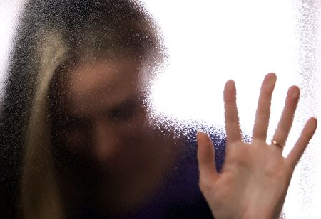 Young blonde behind the glass and touching it Stock Photo - 8117017