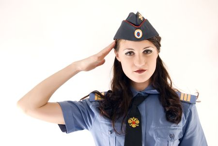 Young beautiful woman in police uniform saluting photo
