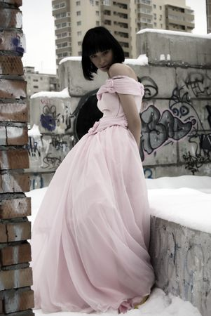 young bride in pink wedding dress standing among street ruins photo