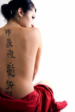 tattoo face: PortrPortrait of the young Asian girl  sitting back to camera