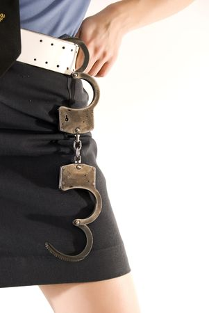 Young woman in police uniform holding handcuffs close-up photo