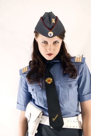Young beautiful woman in police uniform being stern photo