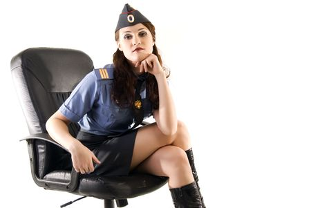 stern: Young beautiful woman in police uniform sitting in the arm-chair