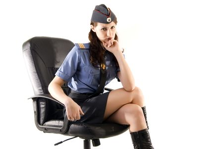 sexy police: young beautiful woman in police uniform sitting in the arm-chair