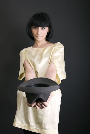 dolorous: Young brunette holding an empty hat  symbolizing poverty and alms Stock Photo