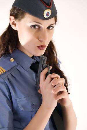 Young beautiful woman in police uniform with gun photo