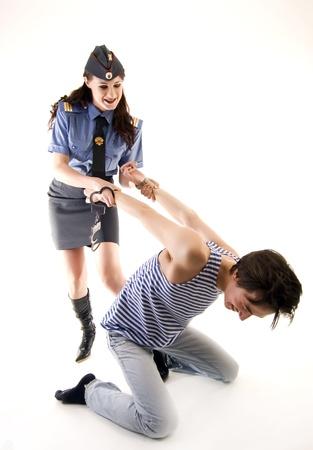 Mujer joven en uniforme de polic�a arrestar a un criminal