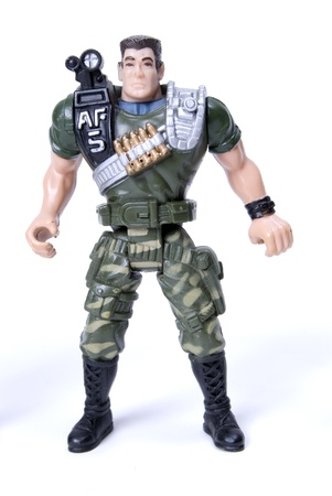 plastic soldier: toy soldier in camouflage  over white background