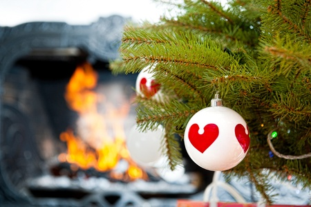 Christmas baubles against burning flame in fireplace on christmas tree isolated on white photo