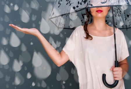 umbrella cartoon: Portrait of beautiful young fashionable woman standing under umbrella and catching fake water drops of rain. Safety concept Stock Photo